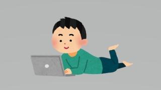 寝そべってノートパソコンを見る男性